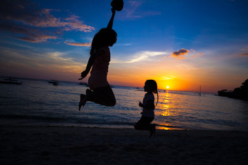 Silhouette of mother and little daughter playing on the beach in
