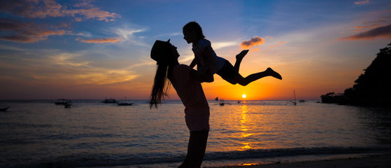 Little girl and her mother having fun at sunset on the island