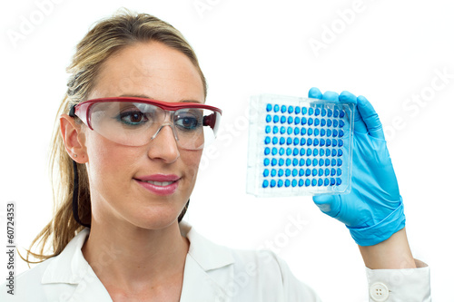 young woman looking a microplate