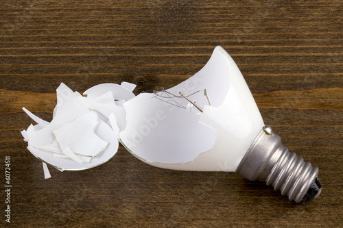 Broken light bulb on a wooden table