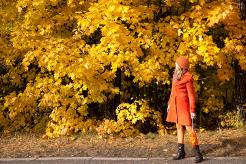 The girl in an orange coat of yellow maple leaves.