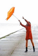 Broken Orange umbrella is flying from the girl.