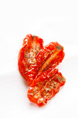 sun-dried tomatoes with olive oil in an old  white wooden backgr