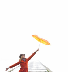 Broken Orange umbrella is flying from the girl.