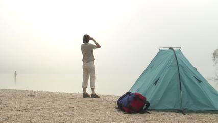 Frau mit Fernglas neben einem Zelt an einem nebligen Morgen