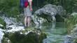 Wanderer mit Rucksack setzt sich neben Gebirgsbach
