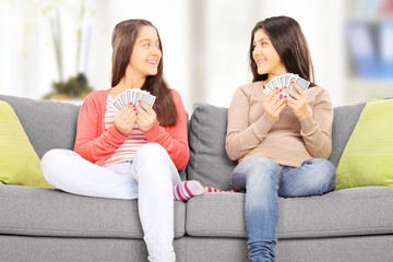 Two teenage girls sitting on couch playing cards, at home