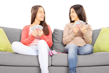 Two teenage girls sitting on couch playing cards
