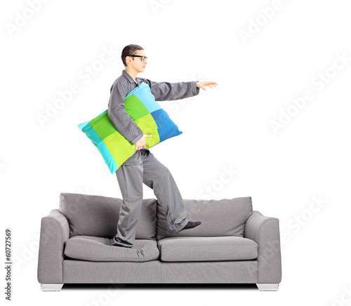 Full length portrait of guy in pajamas sleepwalking on sofa
