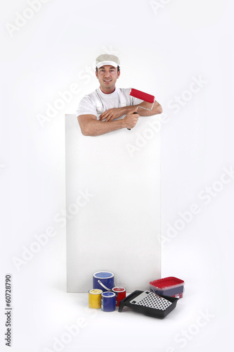 Decorator posing by a poster