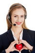 Beautiful caucasian business woman at call center holding heart.