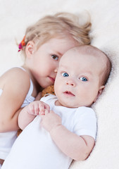 Adorable baby boy and her older sister