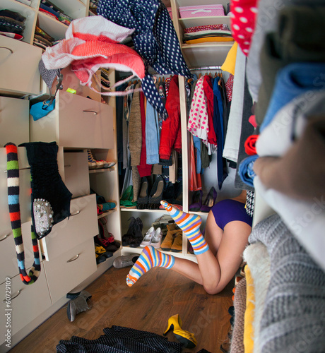 young woman searching for clothing in walk in closet