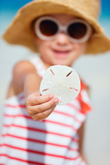 Little girl holding sand dollar