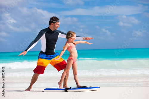 Father teaches daughter how to surf
