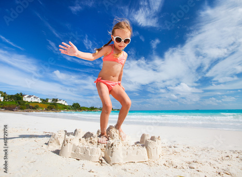 Little girl breaks sand castle