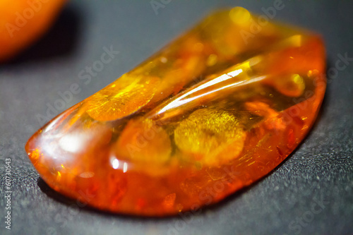 Closeup of amber golden mineral on grey gray background