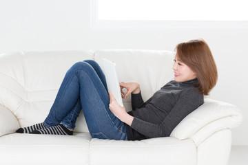 ソファでタブレットを見る女性