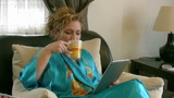 Woman sits on a couch in a living room and using digital tablet