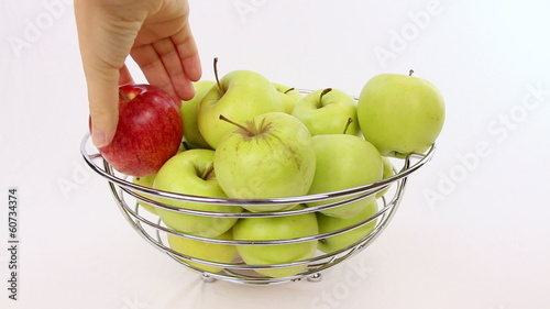 Hand chooses a red apple from a bowl with green apples