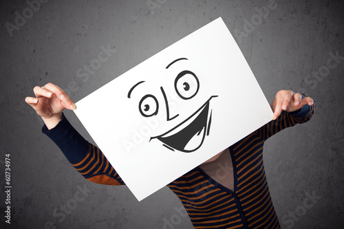 Woman holding a cardboard with smiley face on it in front of her