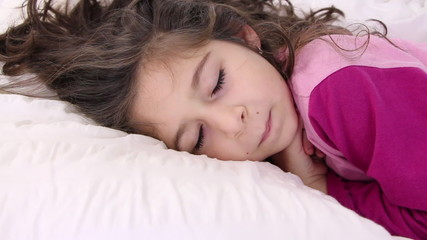 Little girl jumps on a pillow and closes eyes