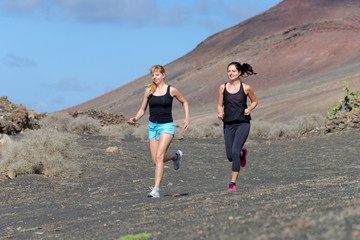 Two female running athletes. Women trail runner sprinting