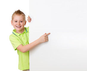 Handsome kid boy pointing to blank advertisement banner