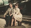 Beautiful vintage style couple sitting on suitcases
