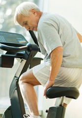 Senior man adjusting seat on a bike machine in a fitness club