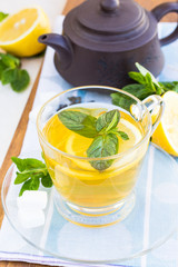 Cup of tea with mint and lemon on a wooden surface