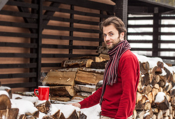 Smiling man with firewood and tea - winter countryside landscape