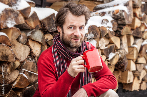 Happy man drinking tea outdoor - winter countryside landscape