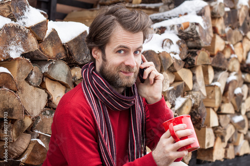 Smiling man talking on a mobile phone outdoor during winter