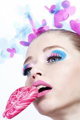 Портрет девушки с ярким макияжем и конфетой в виде сердца
