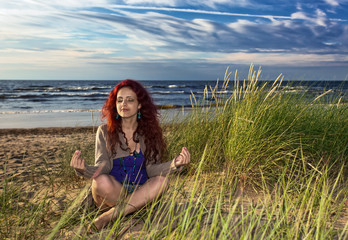young woman meditates on seacoast