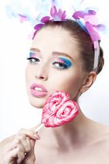Портрет девушки с ярким макияжем и конфетой в виде сердце