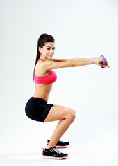 woman doing squats with dumbbells on gray background
