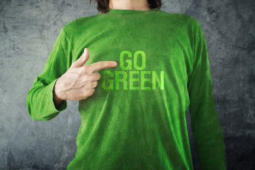 Go green. Man pointing to title printed on his shirt