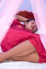 woman sleeping under a mosquito net