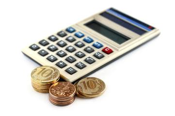Монеты и калькулятор на белом фоне
