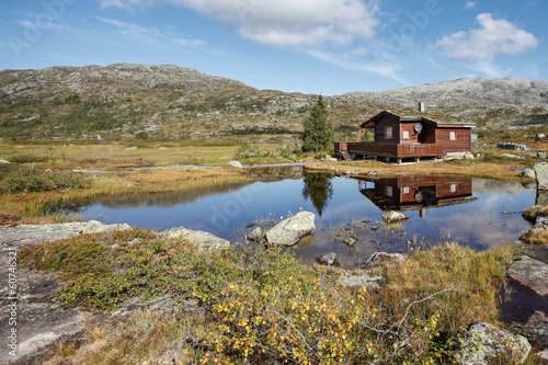 small hut at norwegian lake in hardanger vidda