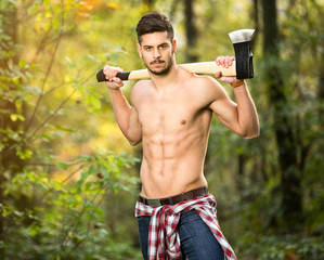 Sexy lumberjack in forest