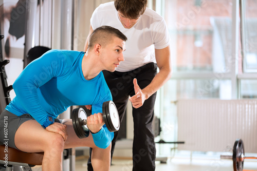 Man doing weights lifting with trainer