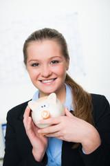 hübsche junge frau mit sparschwein