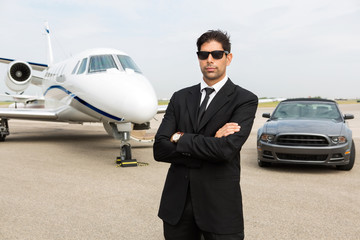 Businessman Standing In Front Of Car And Private Jet