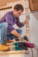 a young carpenter fixing post of ladder