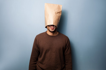 Happy young man with a bag over his head