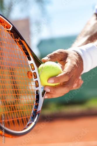 hand with tennis ball and racket