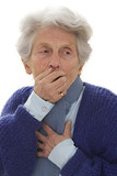 senior woman holds her hand to her mouth while feeling nauseous